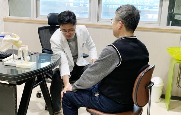 천안우리병원 김태한 관절센터장이 퇴행성관절염으로 내원한 환자의 무릎을 살피고 있다.
